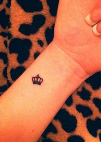 king symbol tattoo on wrist